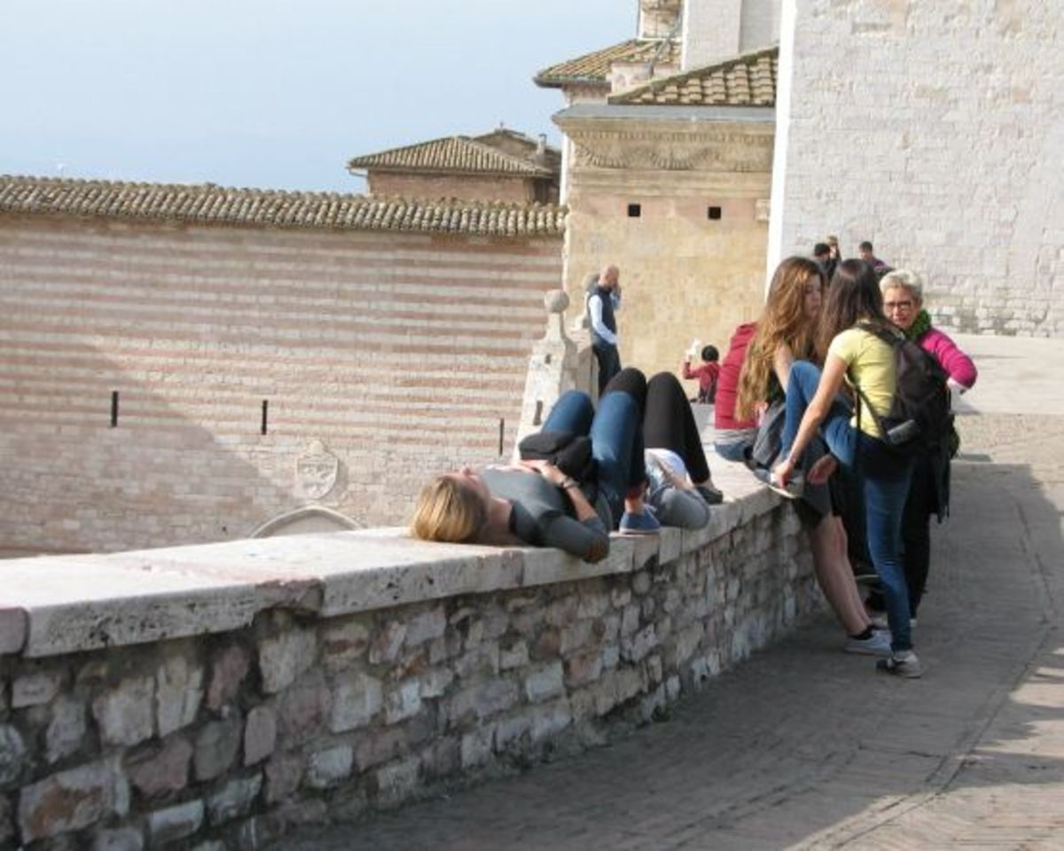 Students enjoying riposo on the retaining wall near the main entrance to St. Francis upper Basilica.