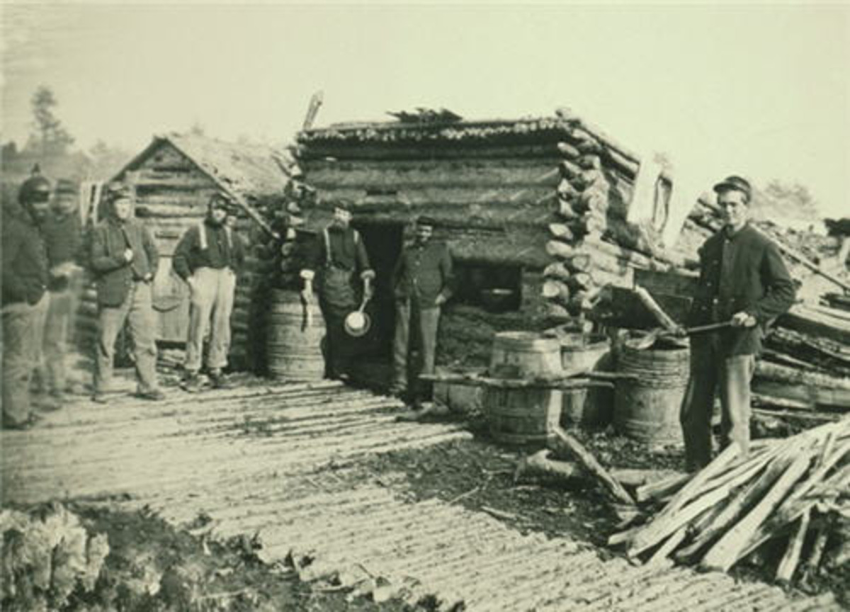 A log hut and a corduroyed Company Street in a winter encampment