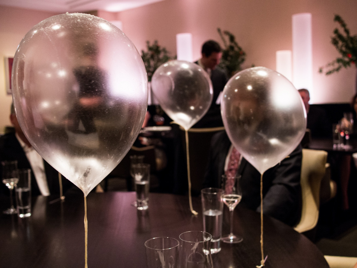 Edible helium balloons floating above a customer's table in the Alinea dining room.