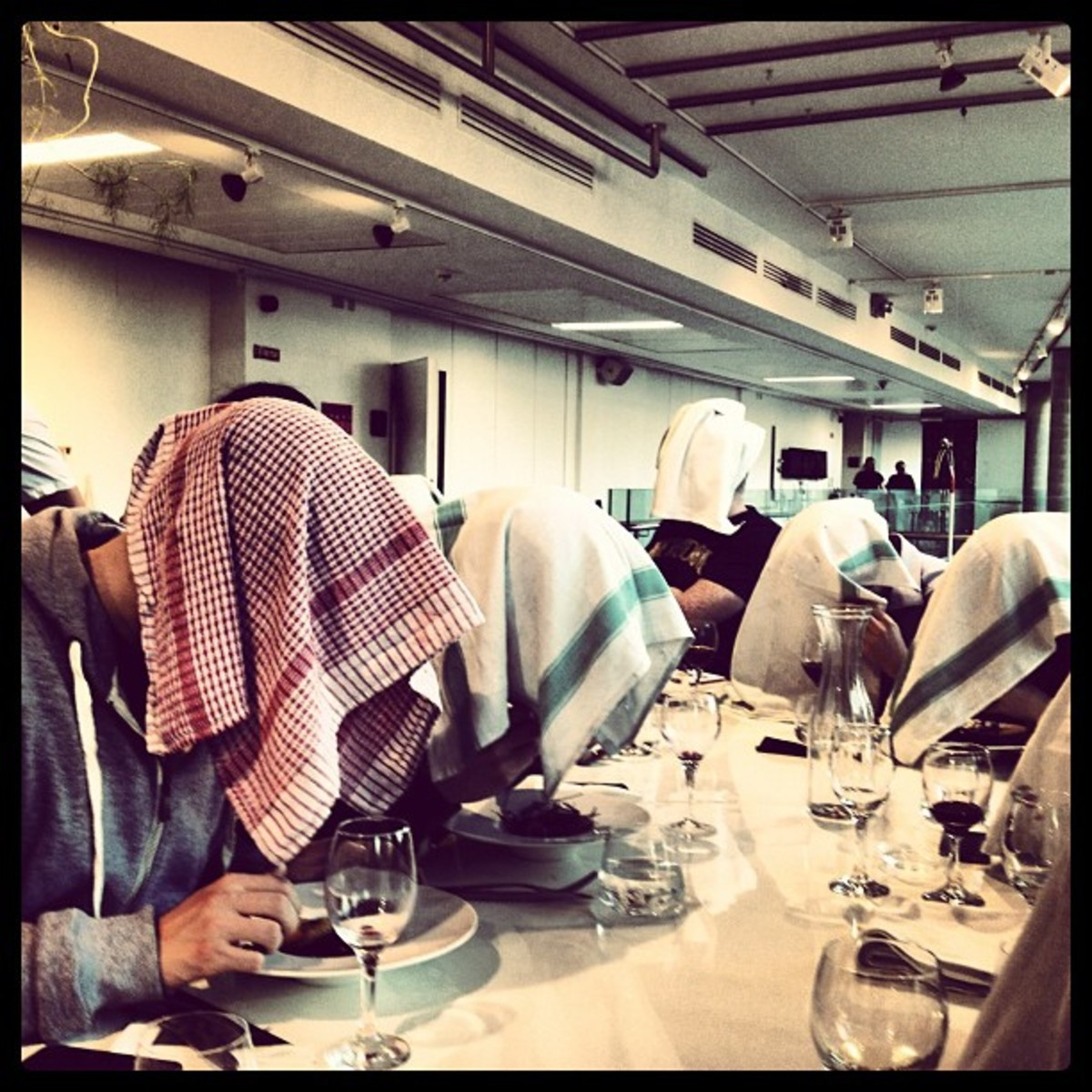 A group of people eating ortolan the traditional way, with napkins covering their heads and faces.