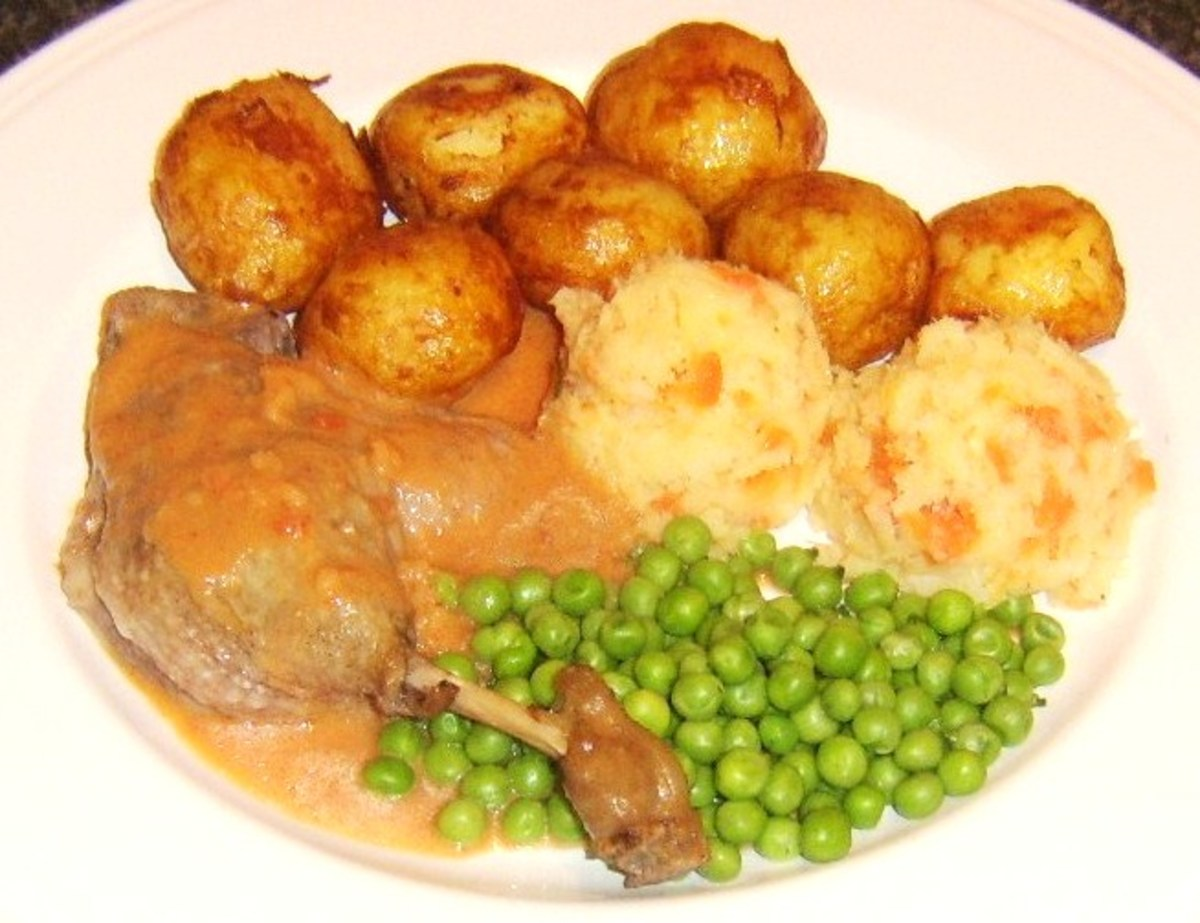Casseroled duck leg with plum sauce, roast potatoes, carrot and parsnip mash and peas
