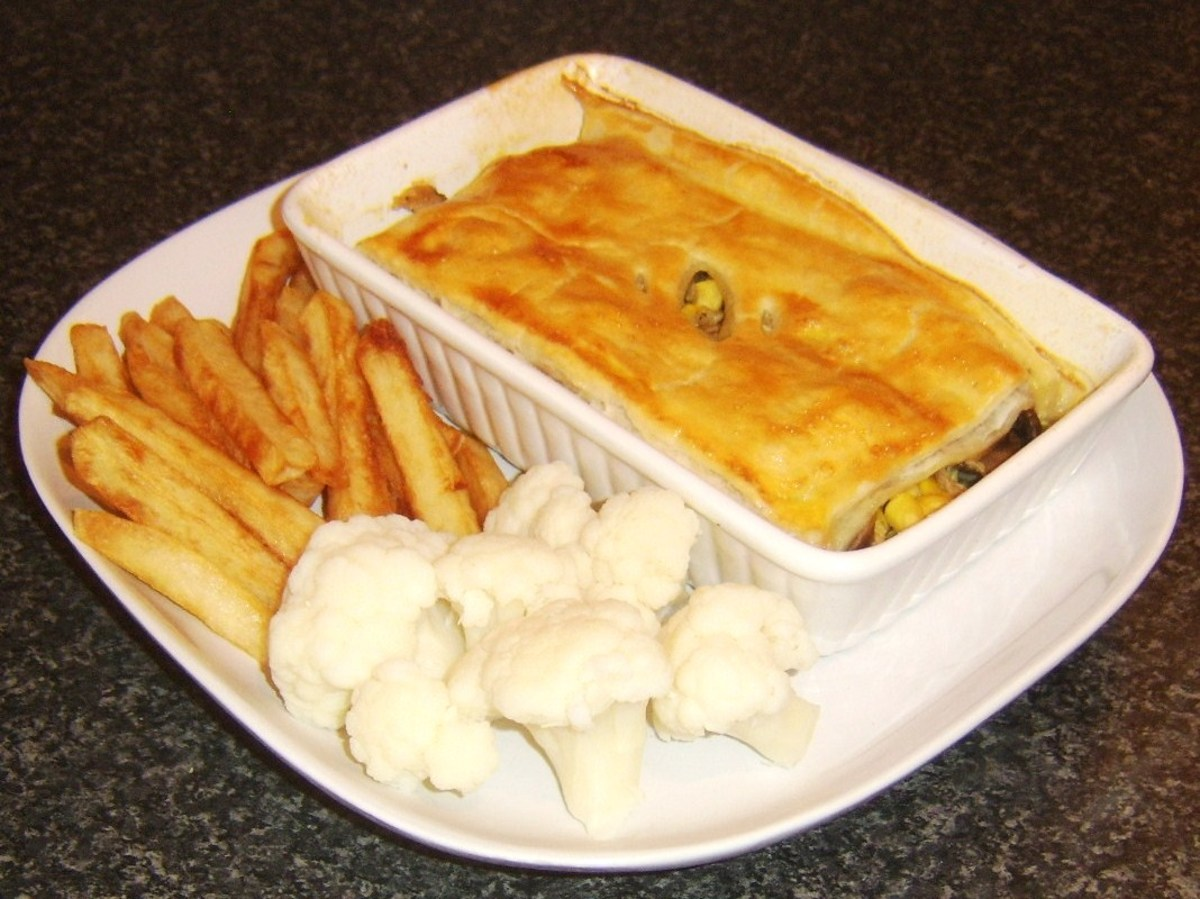 Duck leg meat and mushroom pie served with chips and cauliflower