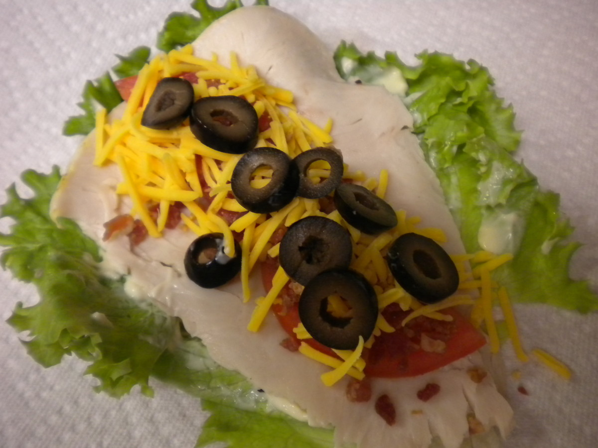 6)Add 2 tbsps grated cheddar cheese.  I personally like to add some slices of black olive - it gives it a little more body & bulks your wrap up so you really have something to sink your teeth into.