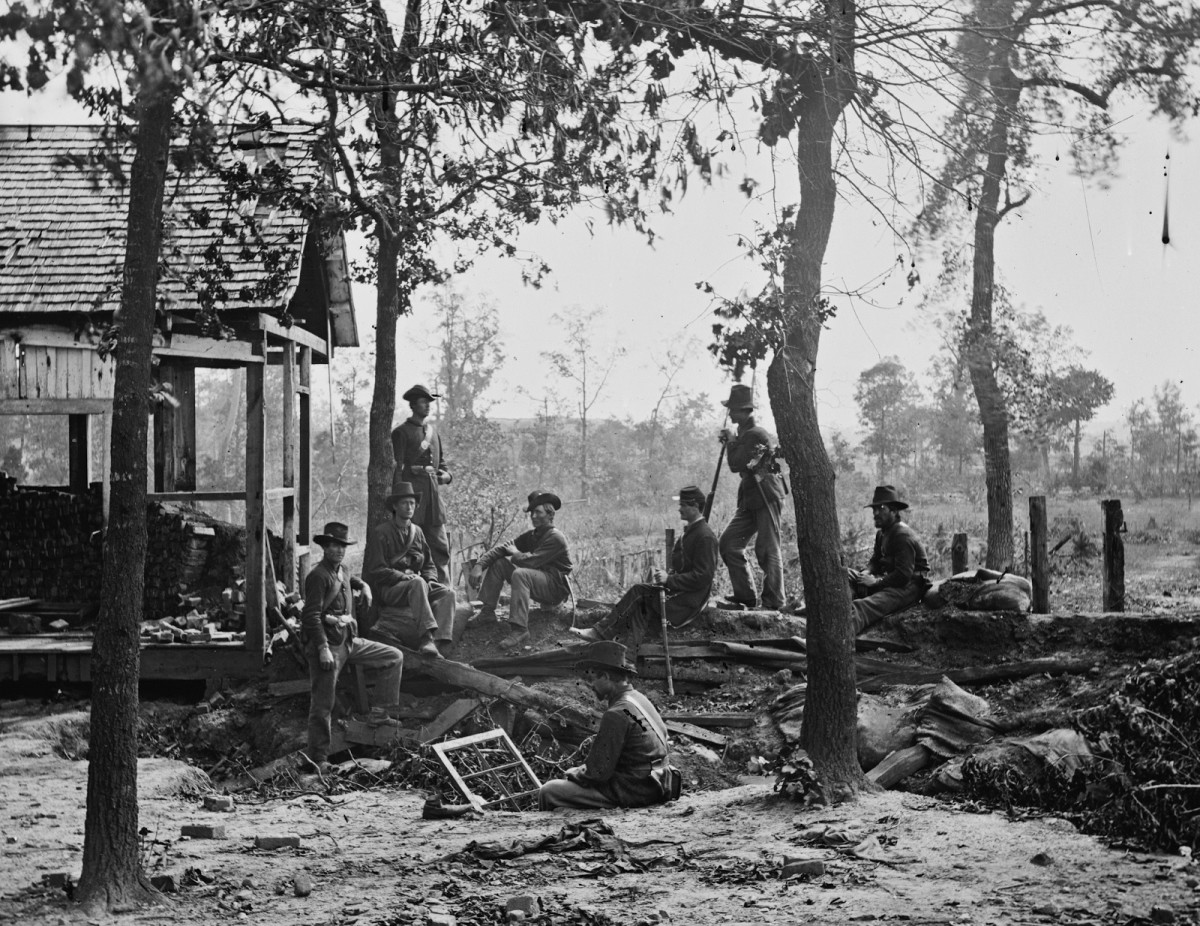Union troops relax near the ruins of a house in VA