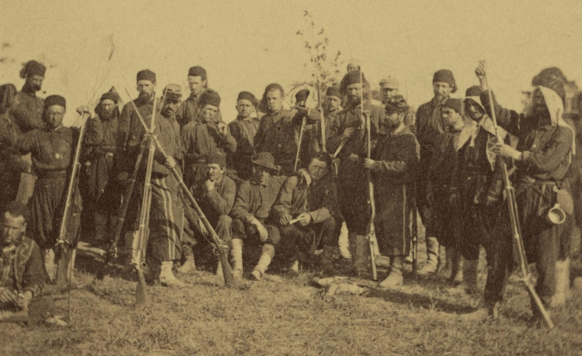 Union Zouave troops pose by a musket stack