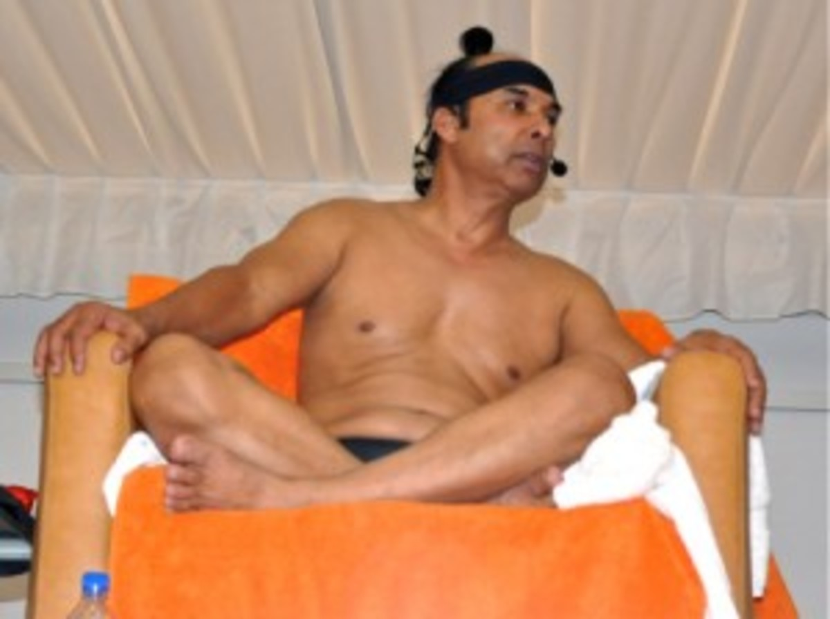 A seated Bikram, teaching yoga