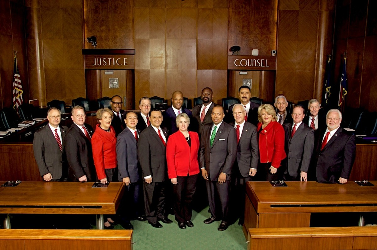 2014 photo of the Houston City Council with Mayor Annice Parker center in red jacket and pearls. These administrators have outlawed poor people from within the Houston city limits and likewise, charities or people from giving poor people food.