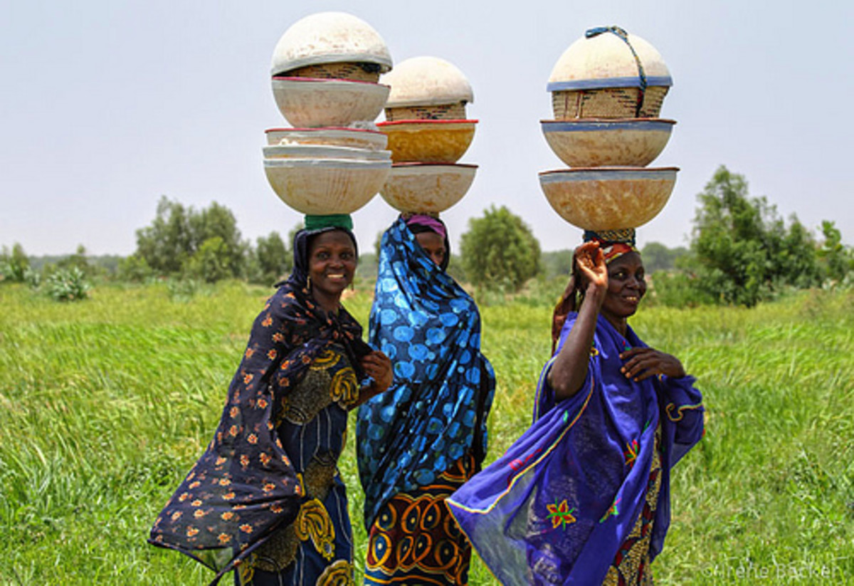 Fulani women carry taking food to their husbands
