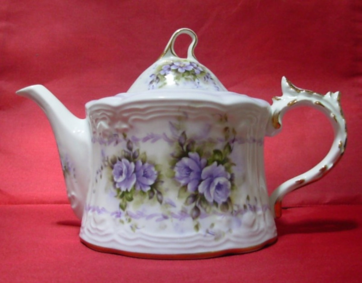 A teapot with a music box on the bottom.