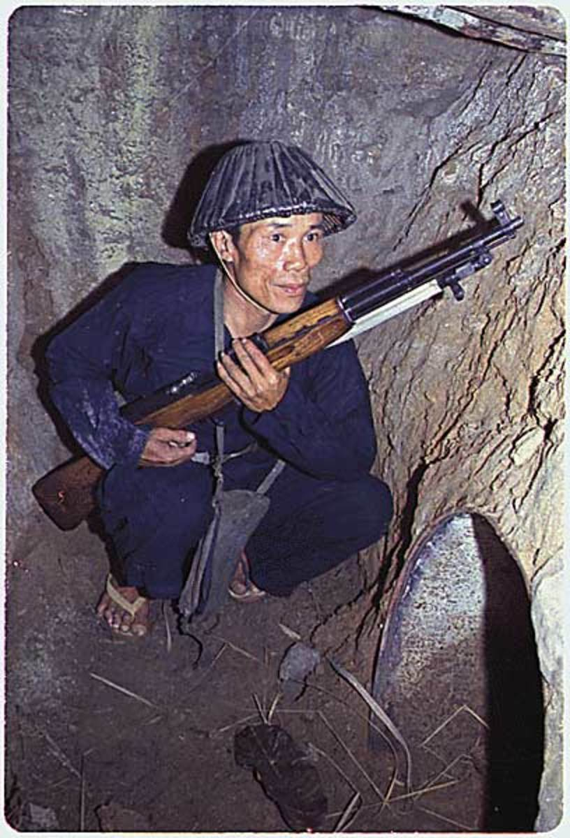 A Viet Cong soldier crouches in a bunker with an SKS rifle.