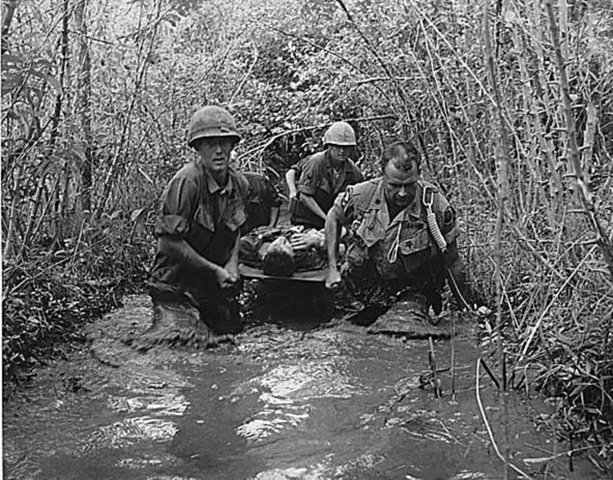Soldiers carry a wounded comrade through a swampy area, 1969