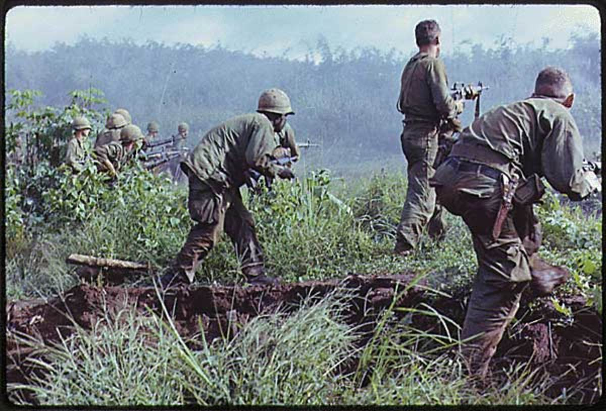 Dak To in South Vietnam. An infantry patrol moves up to assault a Viet Cong position after an attempted overrun of the artillery position by the Viet Cong during Operation Hawthorne.