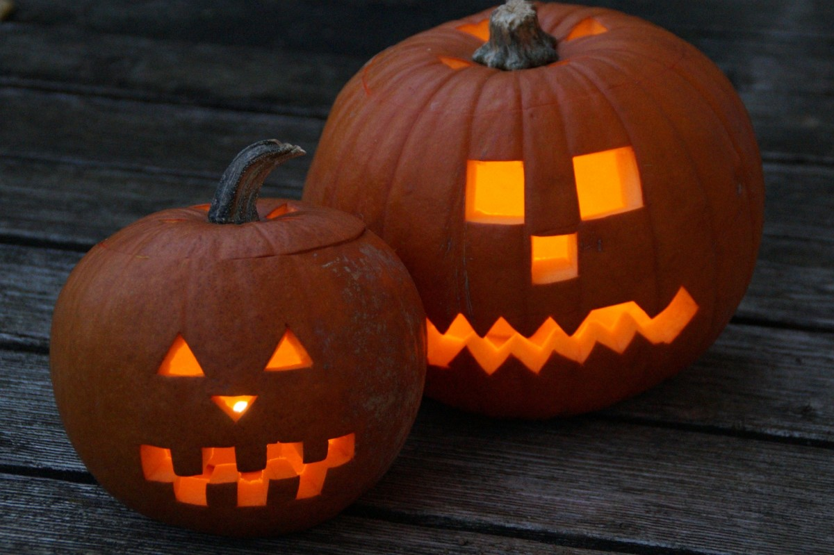 Pumpkins with cut out faces for Halloween. Lit candles placed in the pumpkin light up their faces.