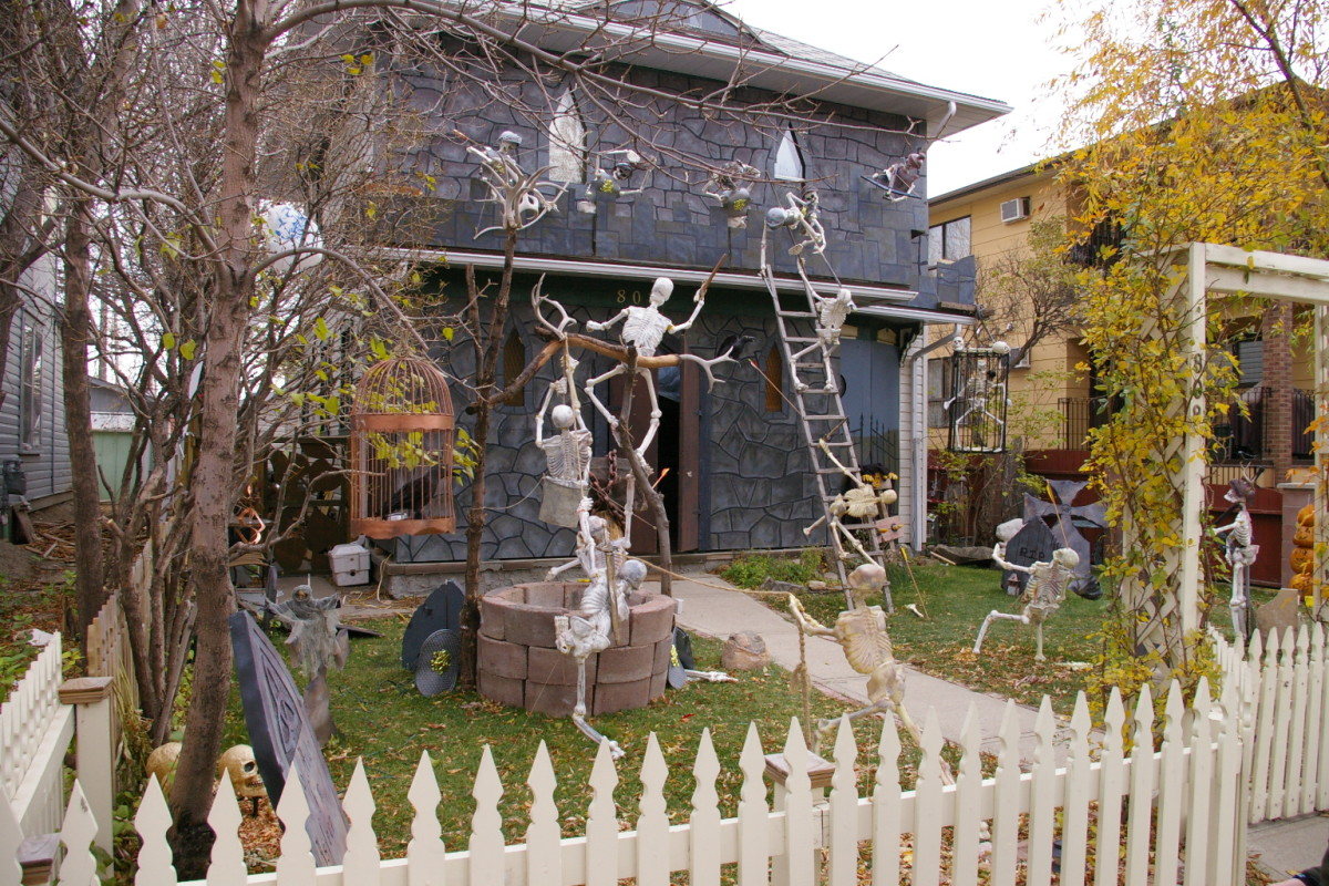 A haunted gray house with a variety of skeletons posed for action..