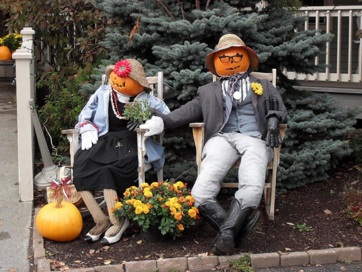 A couple of pumpkin jack-o-lanterns dressed as a man and a woman sitting in chairs in a flower bed.