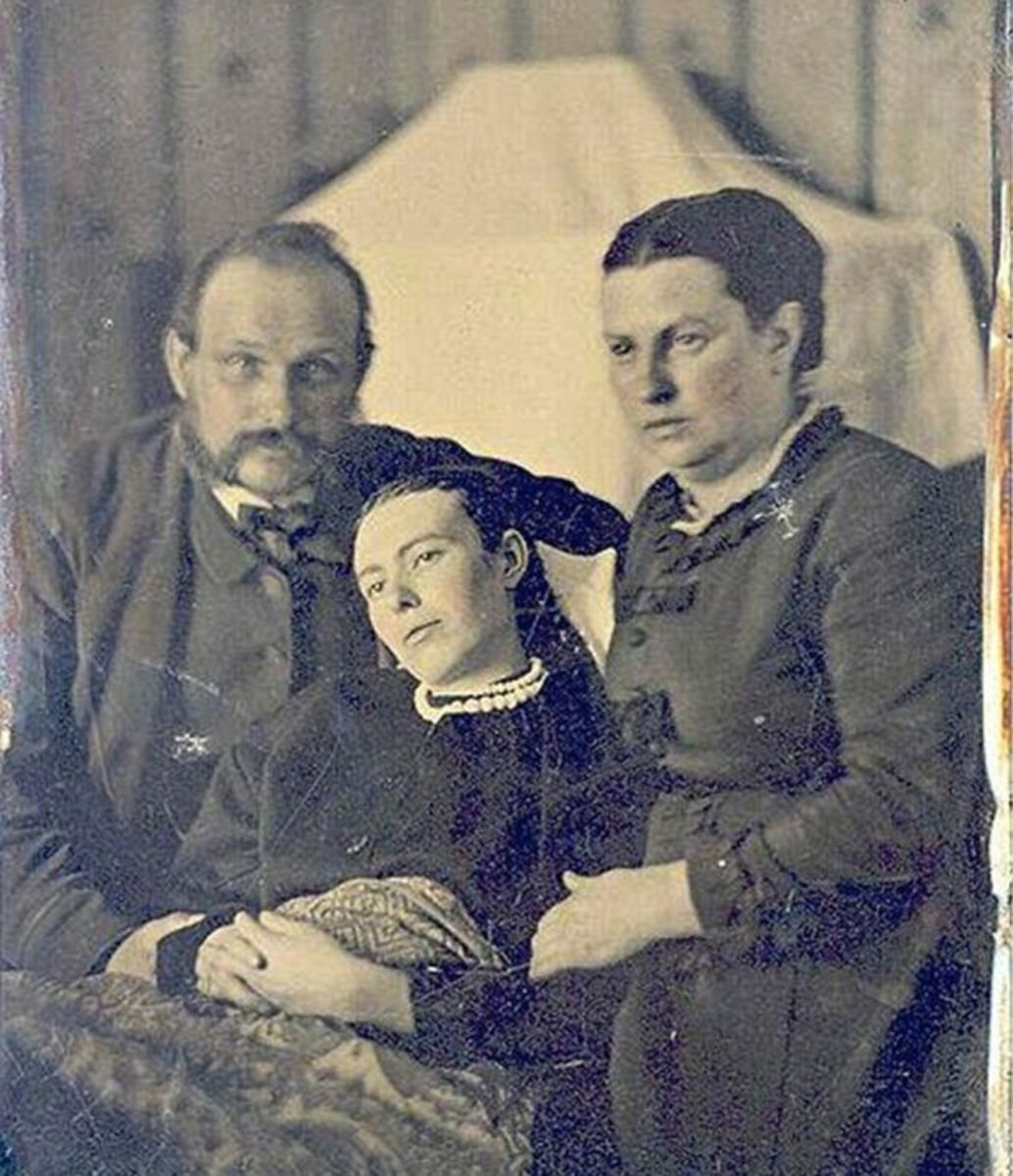 Two parents pose for their one and only family portrait with their deceased daughter, a likely victim of scarlet fever or tuberculosis.
