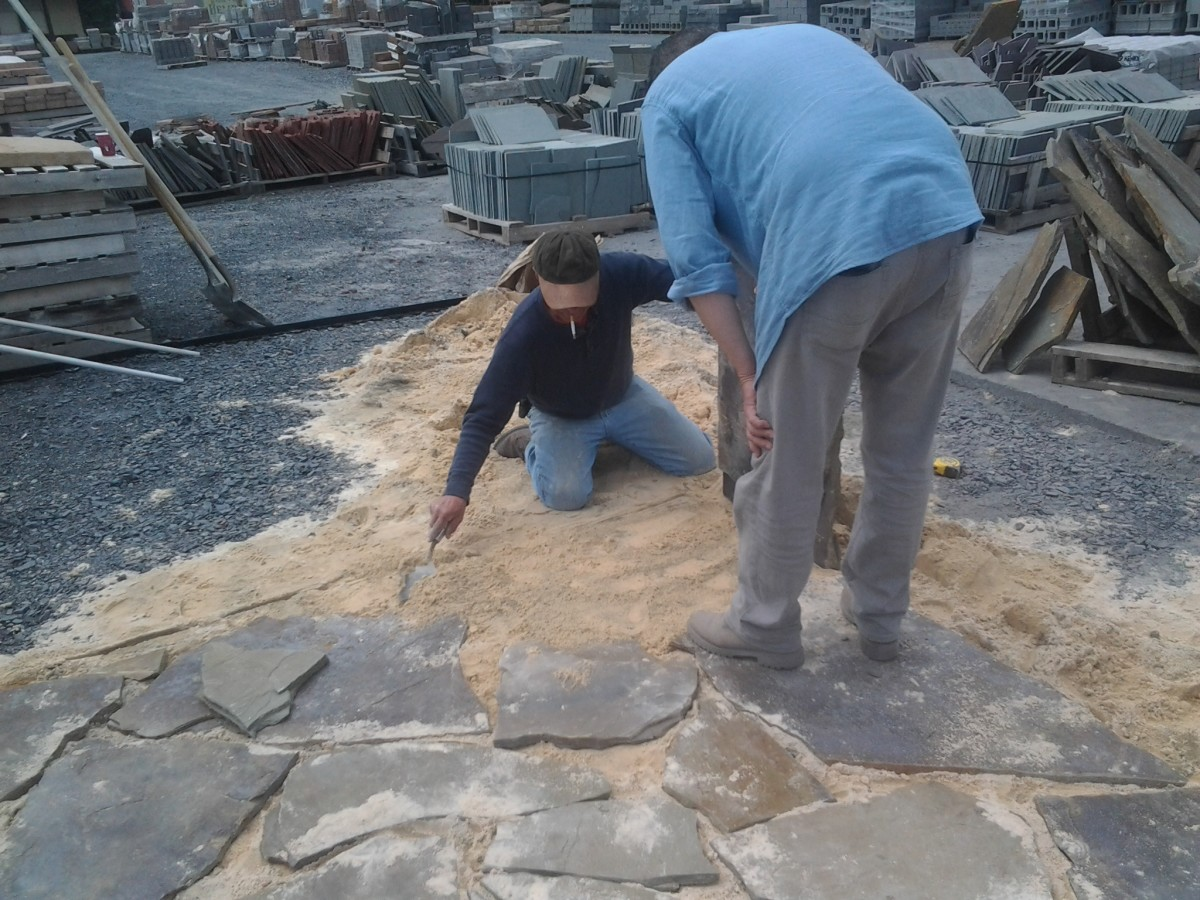 c. On hands and knees to carefully place the unevenly shaped stones.