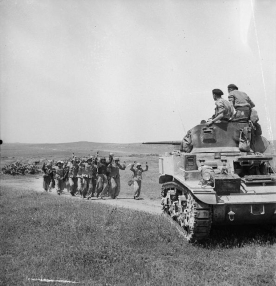 German prisoners led by an Allied tank over 200,000 Axis troops surrendered in Tunisia.