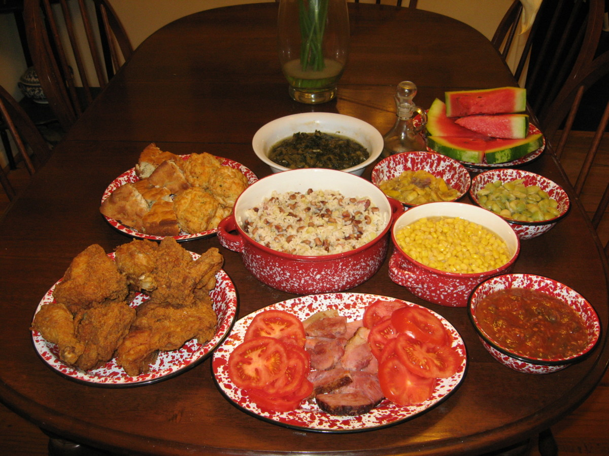 A Gullah-Geechee dinner at my house. Clockwise, from top: turnip greens, pepper vinegar, squash, watermelon, lima beans, corn, okra and tomatoes, fresh tomatoes, cured ham, fried chicken, crackling bread, and biscuits. Hoppin' John is in the center.