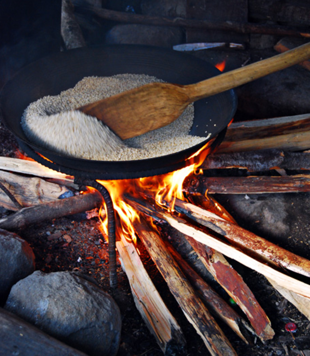 Roasting the rice in a large wok and stir continuously with a wooden paddle to avoid burning (Image Credit: AkosiSuperEdwinK from pinoyphotography.org)