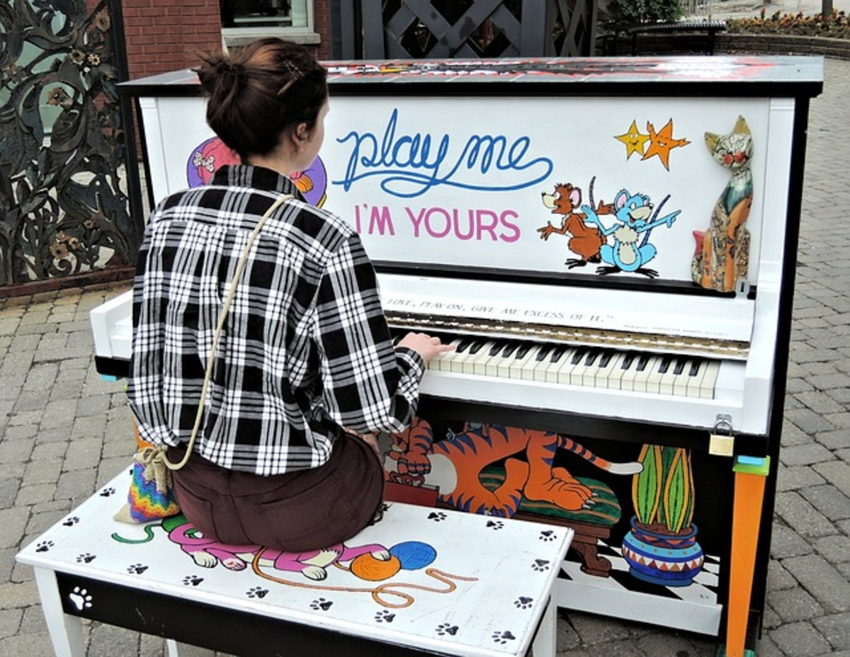 A young girl playing a piano in the outdoors to entertain others.
