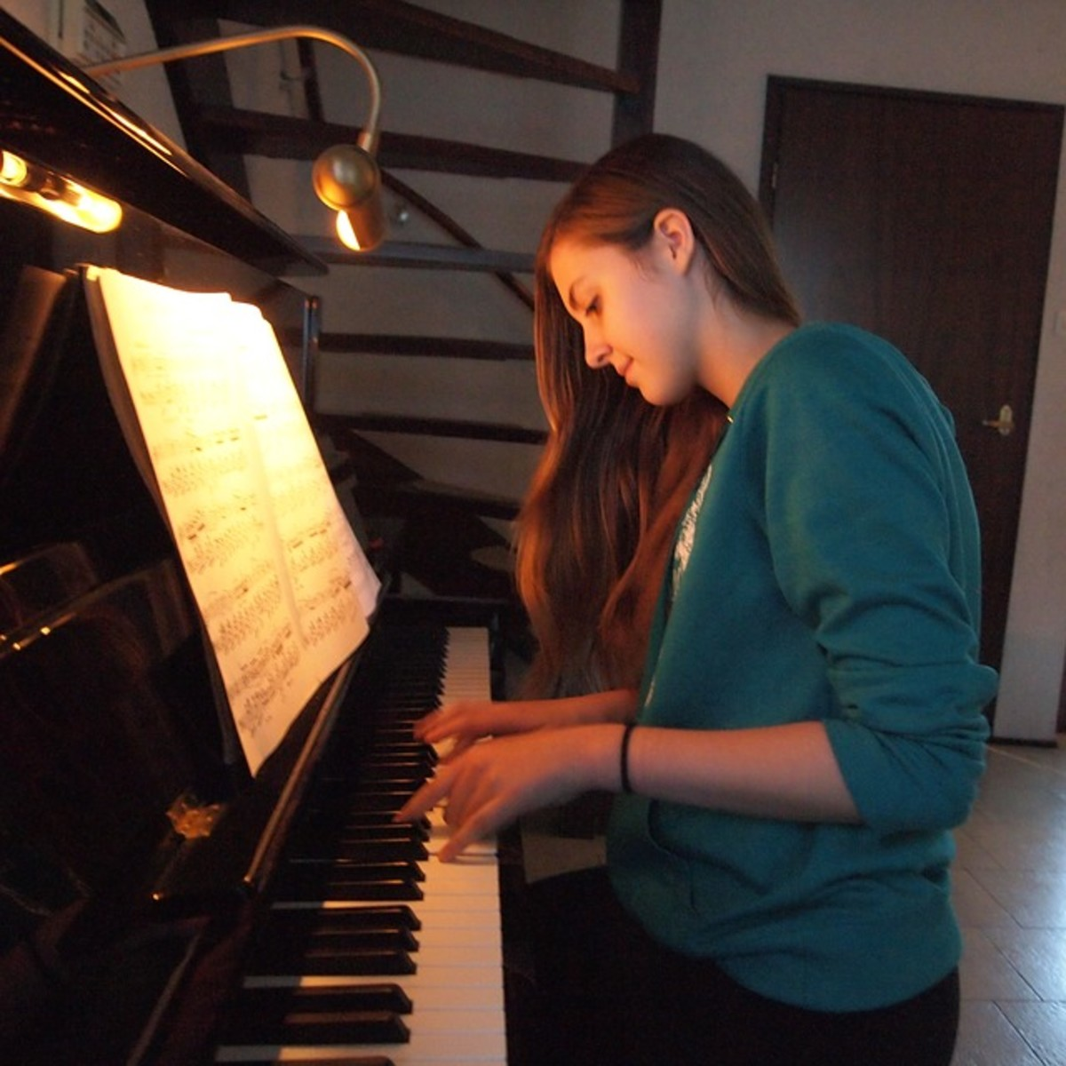 A young woman playing her piano during some free time to make her happy and bring joy.