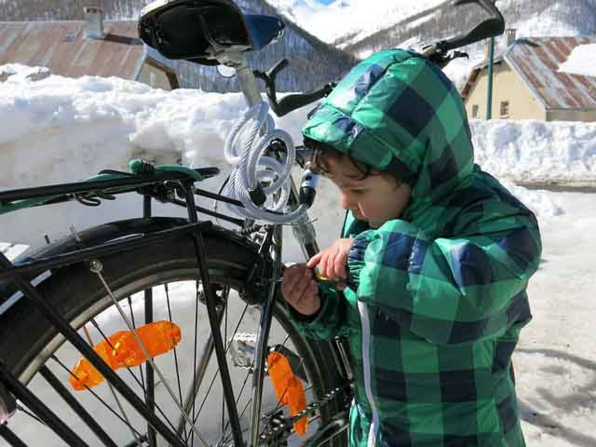 A young man making minor repairs on is bike.