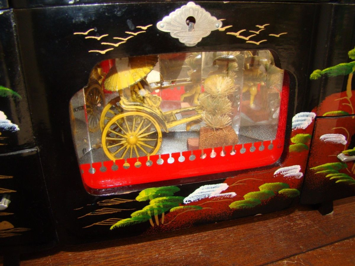Wonderful vintage made in Japan large Jewelry Music box with a Oriental theme, and a Rickshaw that moves behind the glass to the Music being played. It is 13 inches long by 8 inches tall  and 6 inches wide.