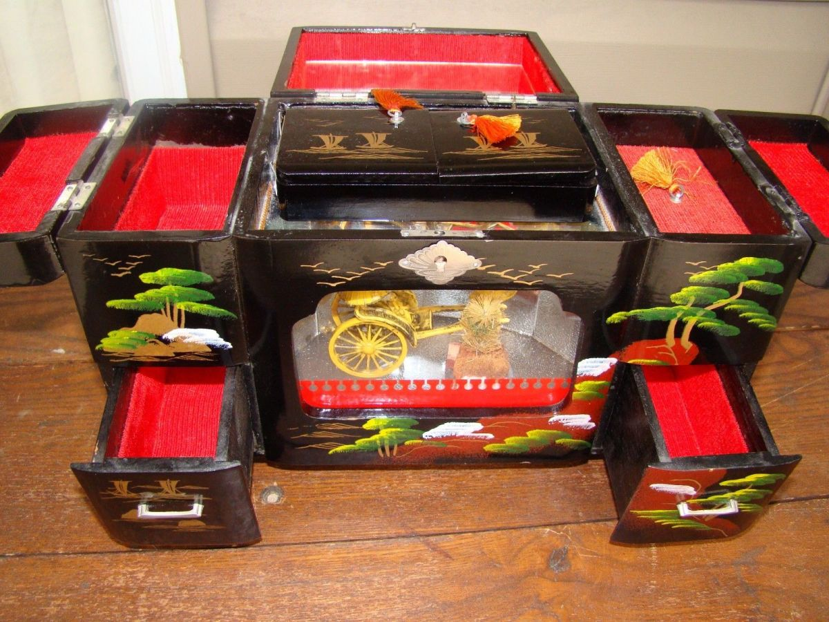 He is a beautiful vintage Japanese jewelry music box  that is good large size with an oriental theme. Made of  black lacquer- with a rickshaw In its glass display.