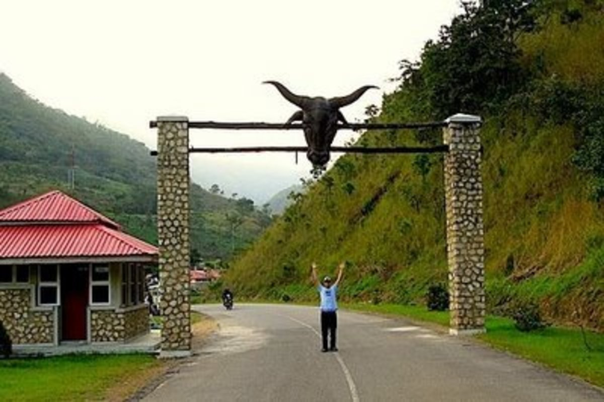 A tourist raising hands in front of the entrance of Obudu Cattle Ranch in Calabar, Nigeria