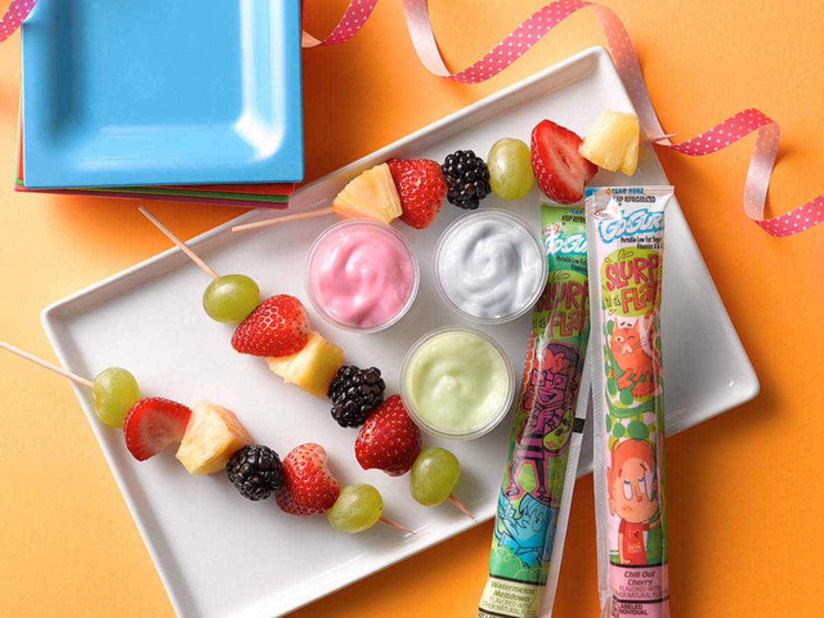 Grapes, pineapple, strawberry, blackberries on skewers with yoghurt as dip.