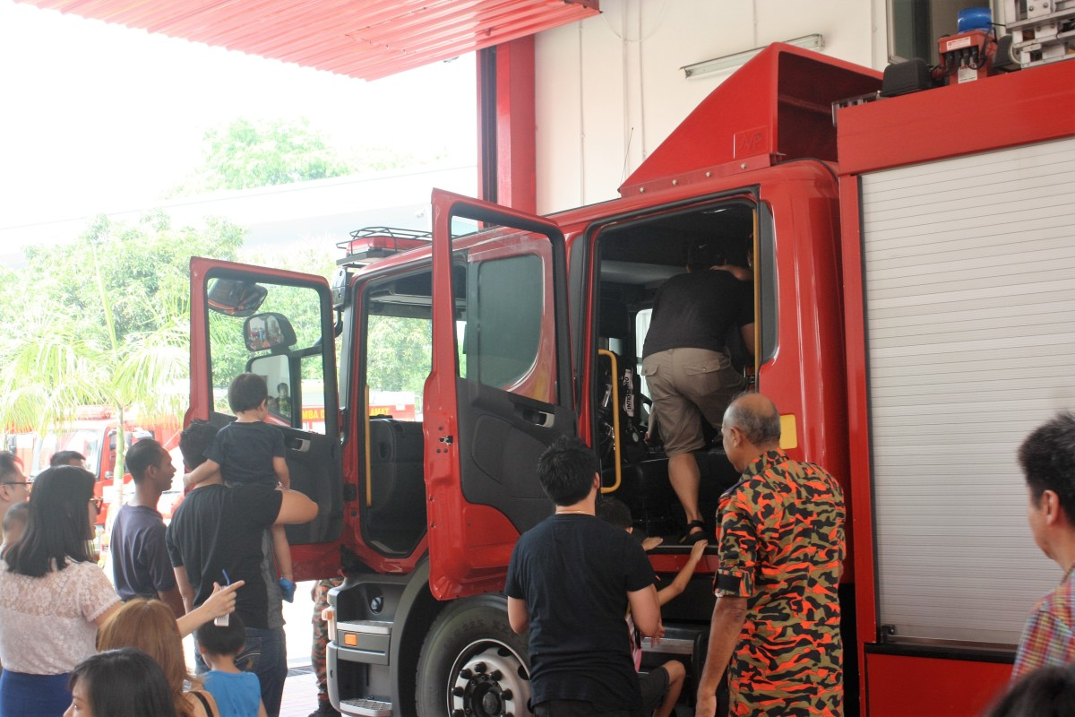 Kids getting into the fire engine with their parents