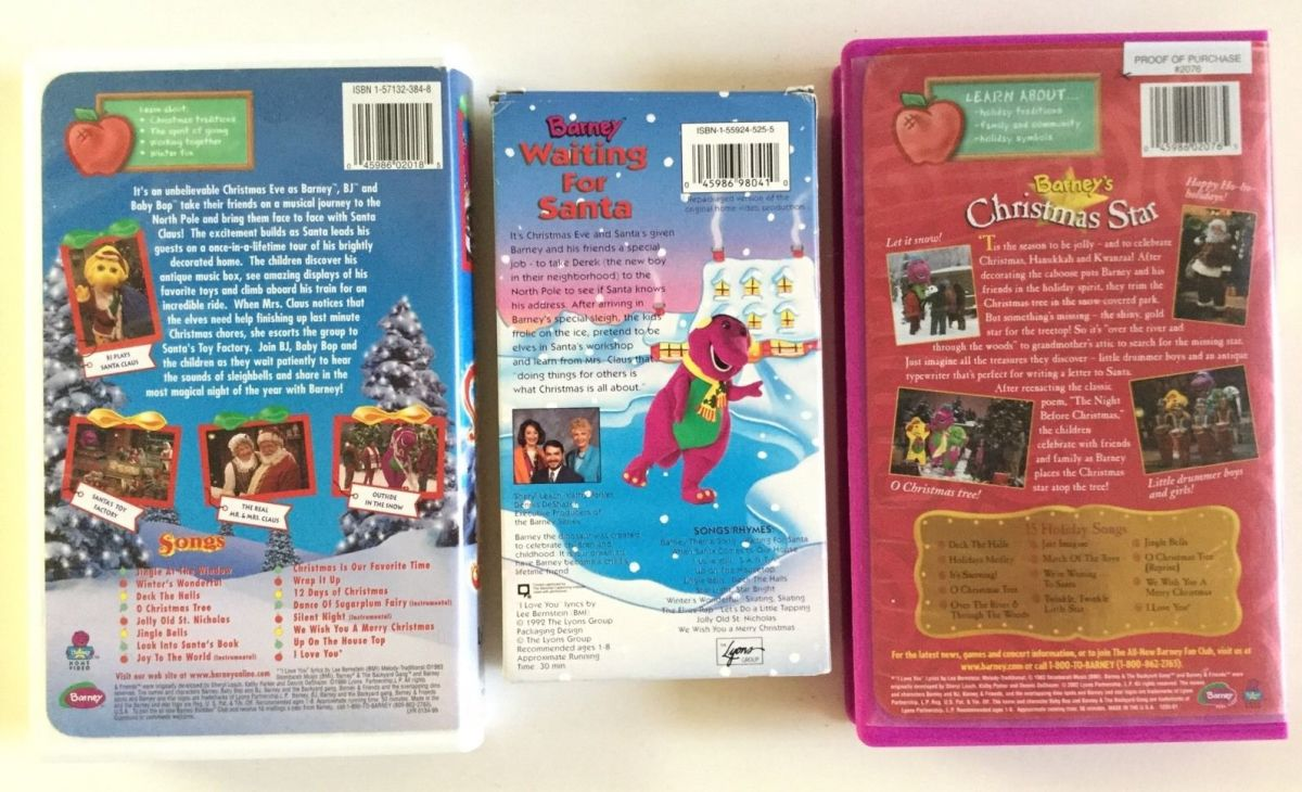 This photo is of the back side of the outside cases of the three Barney Christmas VHS videos, Waiting For Santa, Barney's Night Before Christmas, Star