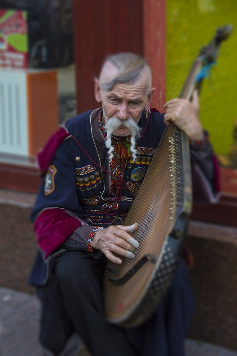 A Ukrainian wearing traditional garb, playing the bandura (a Ukrainian, plucked string, folk instrument)