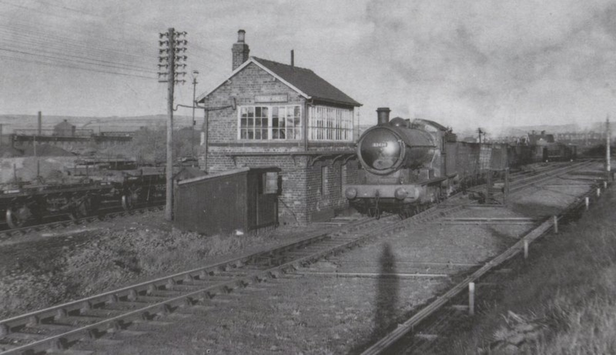 Unidentified Q6 brings a train of mineral wagons past Crag Hall signal cabin near Skinningrove Works