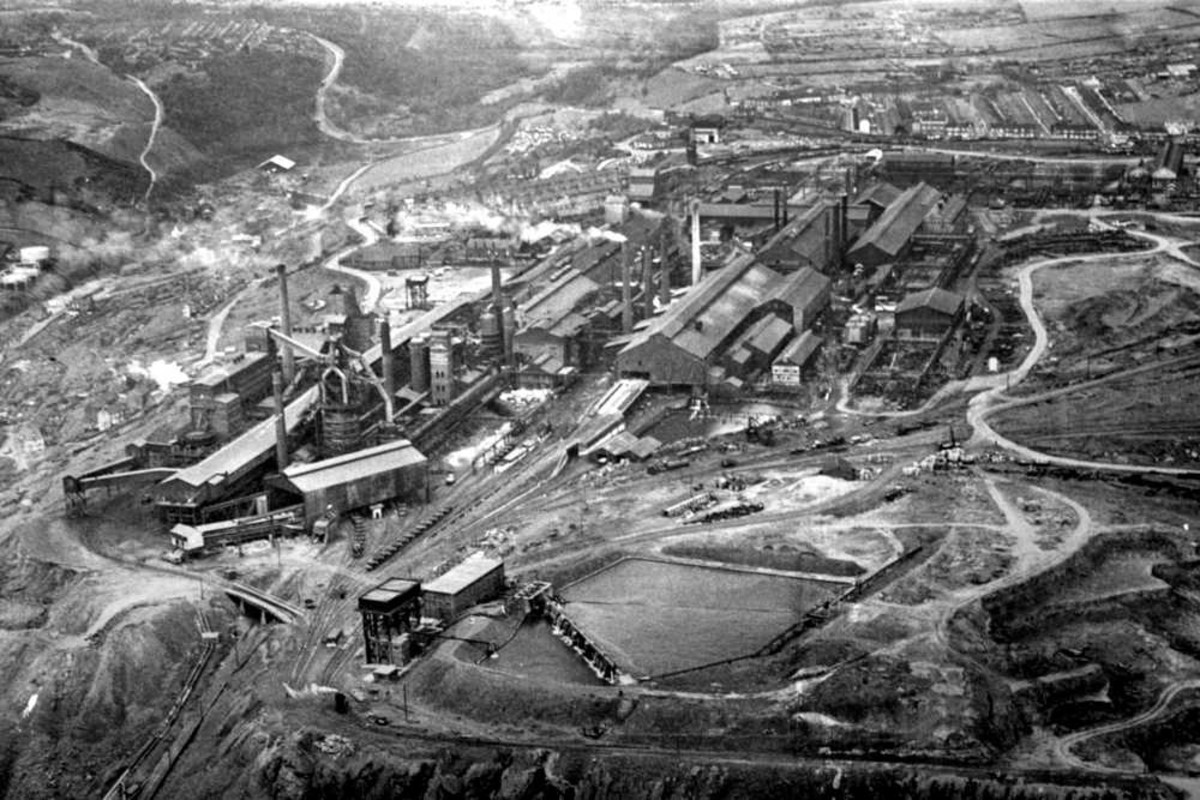 Looking west over Skinningrove Iron & Steel Works. To the left is Skinningrove village ('Shining Grove') with its drift mine. Top left is the zig-zag road uphill to Loftus and Whitby. At the back is the village of Carlin How at the edge of the Moors