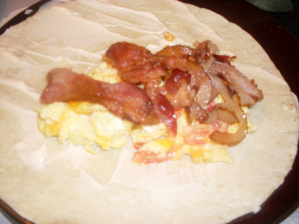 layering the bacon and onions on top of the eggs and tomatoes