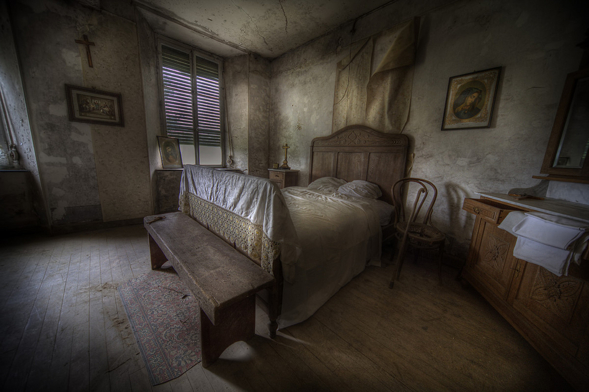 A sparsely furnished bedroom in the farmhouse reveals little comfort aside from the bed itself