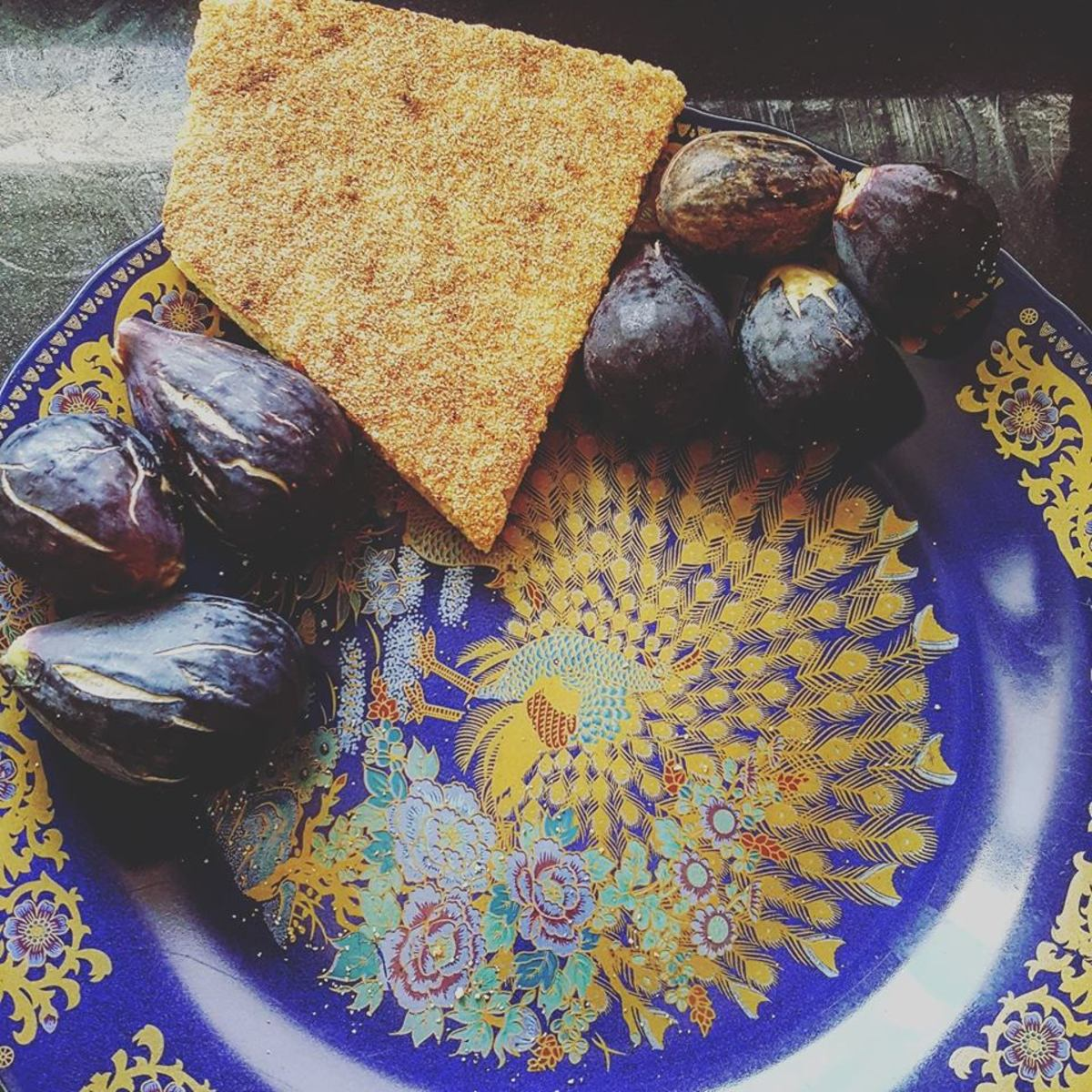 Fresh figs from Kenitra, Morocco, surround a slice of harsha.  The plate is adorned with a peacock - a common design found on many platters.
