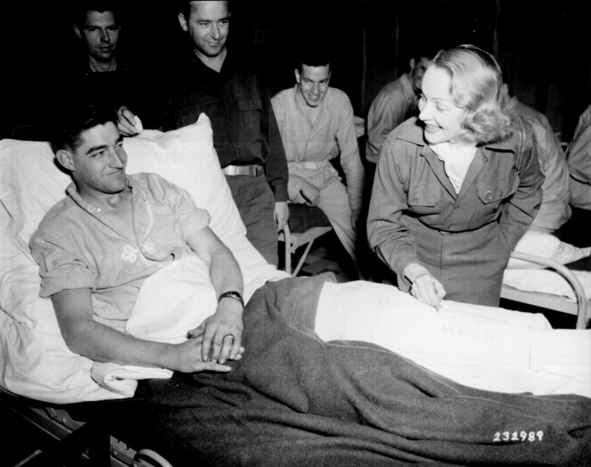Dietrich signing a soldier's cast in Belgium November 1944.