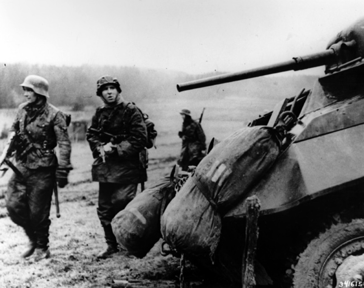 German troops passing by an abandoned American armored car as American troops quickly retreat toward safer ground.