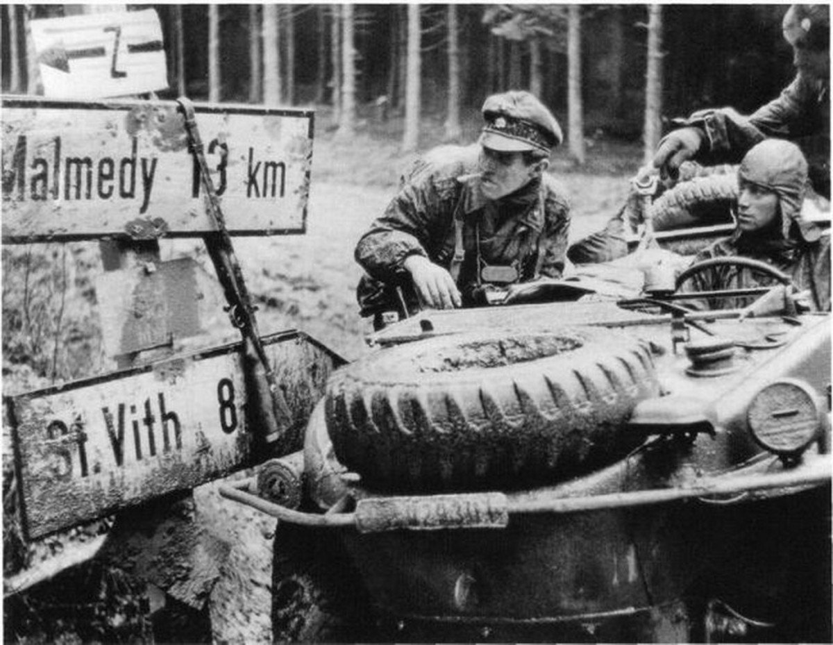 Checking a highway sign at an Ardennes crossroads, an SS soldier from the 1st SS Panzer Division in an amphibious vehicle confirms a path to advance.
