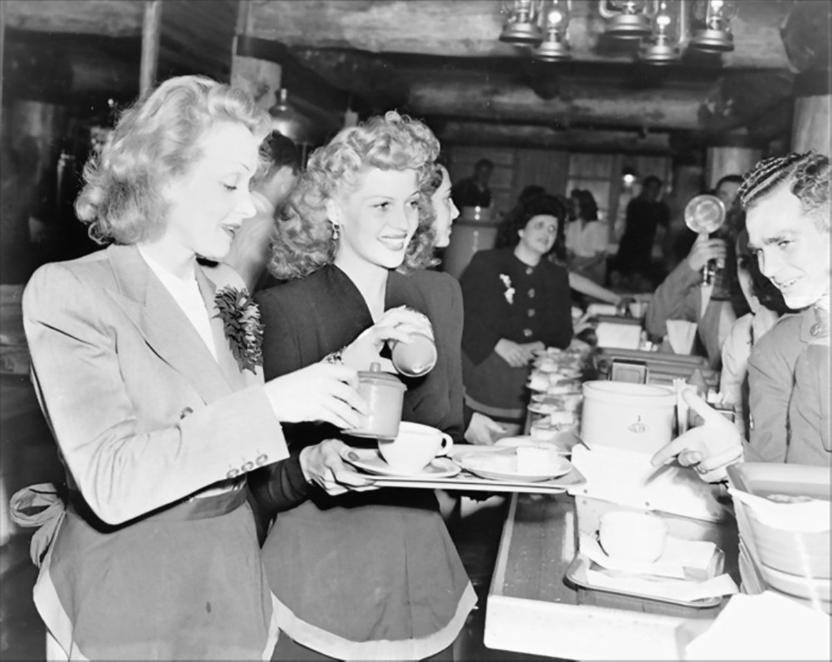 Marlene Dietrich and Rita Hayworth serve food to soldiers at the Hollywood Canteen Los Angeles California (17 November 1942).