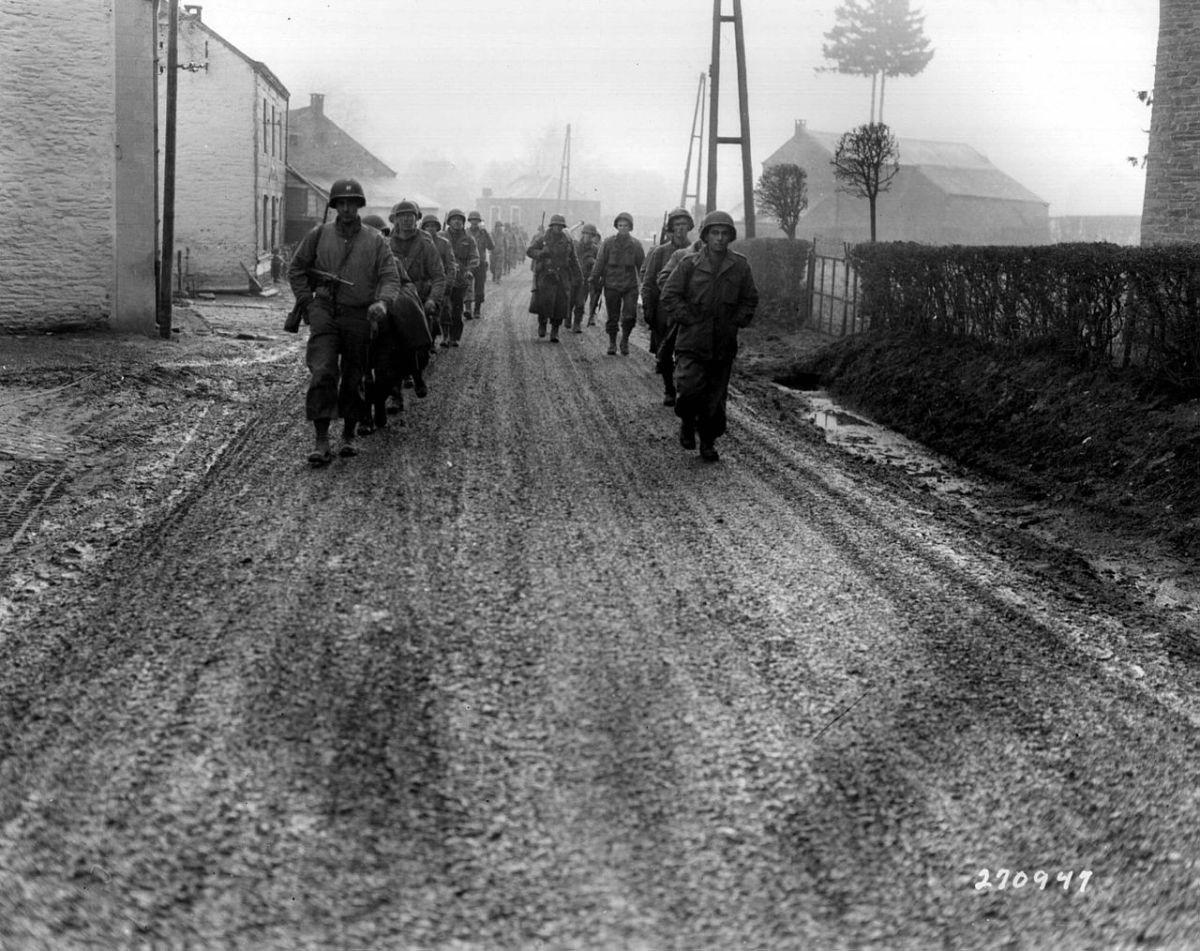 "The 28th Infantry Division ""Iron Division"" walking the streets of Bastogne shattered before the advancing German spearhead some without weapons just four months after their triumphant  parade through Paris in the summer of 1944."