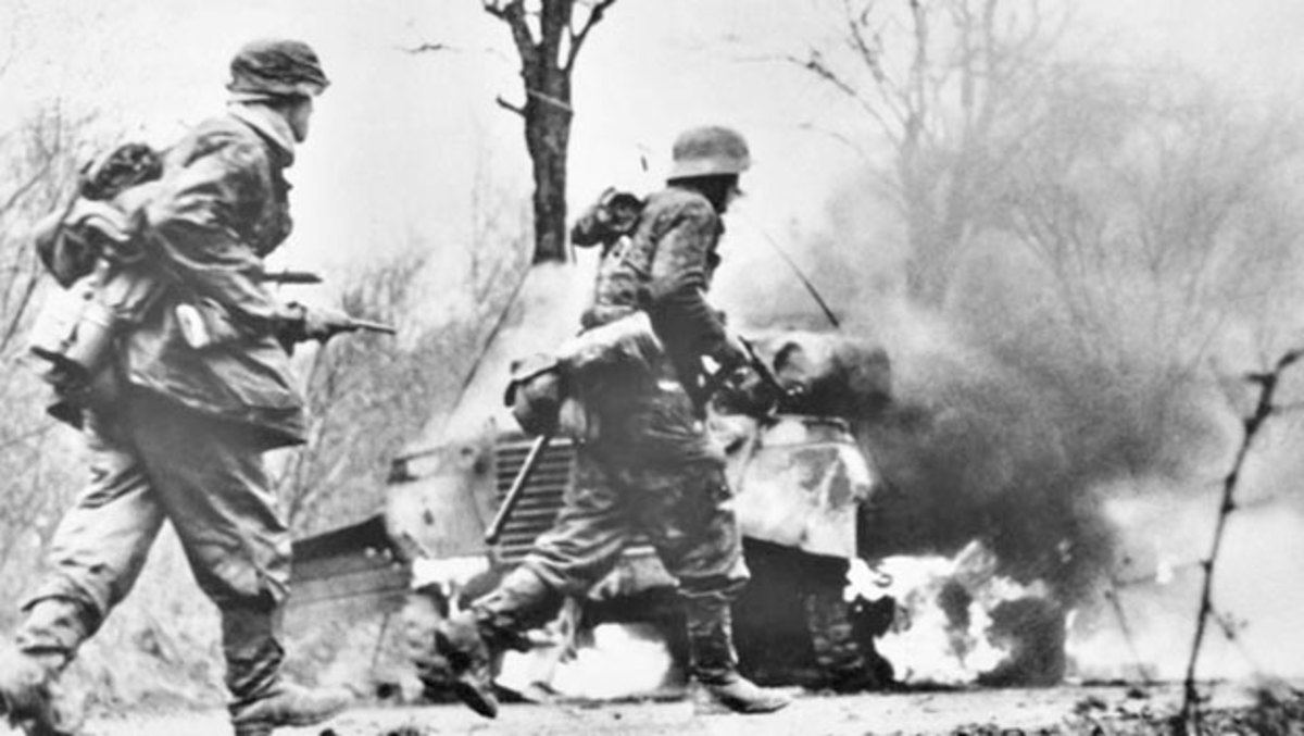 German troops advancing past abandoned American equipment early in the Battle of the Bulge.