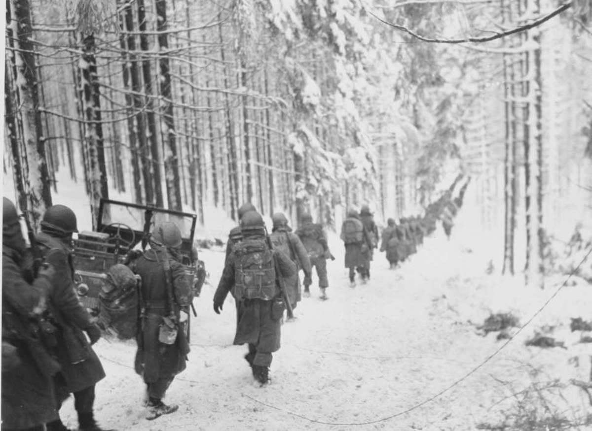 American troops walking along a path in the snow December 1944 in the Ardennes.
