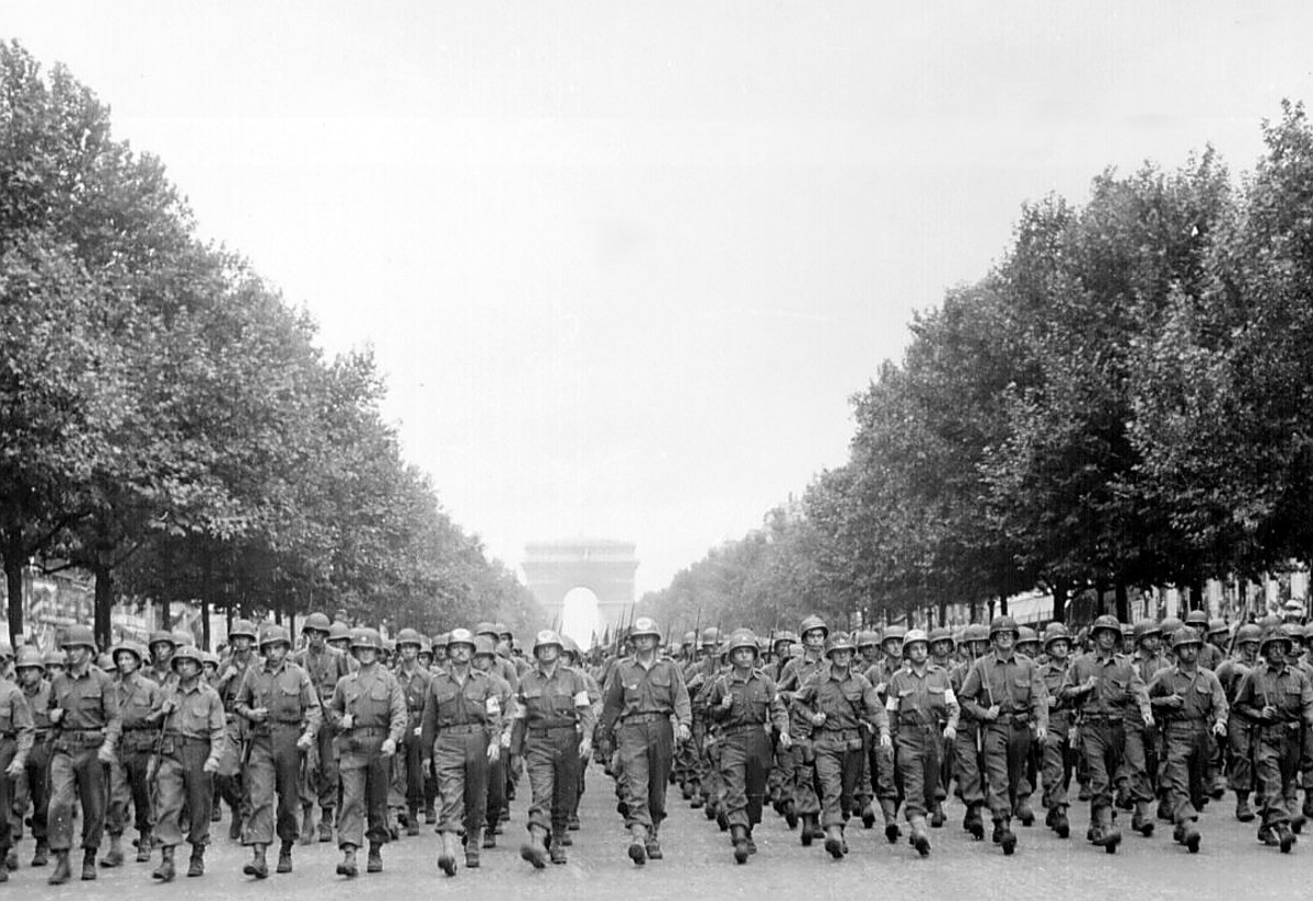 """Men of the 28th Infantry Division march down the Champs Élysées in Paris straight to the battlefield August 29,1944. General Pershing gave it the name the """"Iron Division"""" during the First World War."""