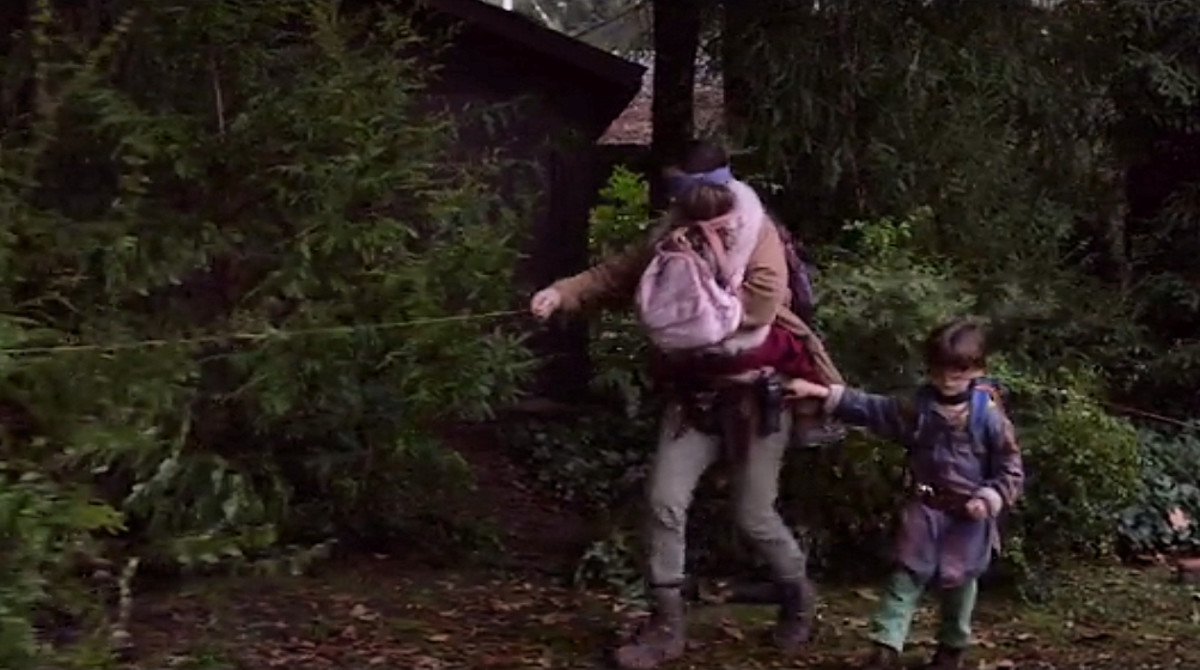Malorie carries Girl and guides Boy along the path to the riverbank in 'Bird Box' (2018), a Netflix Original.