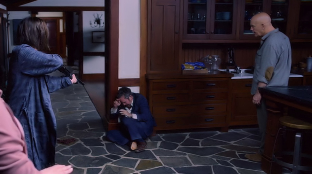 Malorie (Sandra Bullock) and Douglas (John Malkovich) grill Gary (Tom Hollander) at gunpoint when he arrives at the house in 'Bird Box' (2018), a Netflix Original.