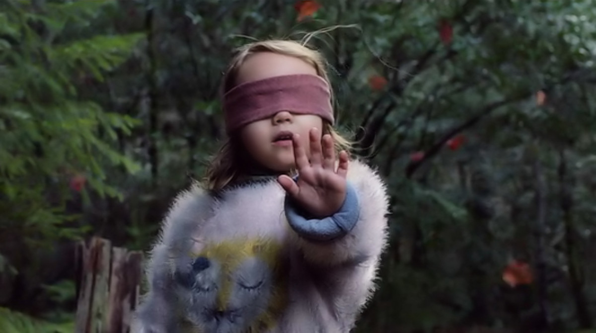 Leaves swirl and Girl's (Vivien Lyra Blair) hair stands on end as the creatures draws near in 'Bird Box' (2018), a Netflix Original.